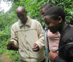 Denis shows his students seeds germinating from elephant dung at the Bwindi Impenetrable National Park.