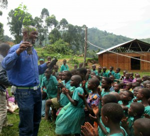 At the Nyarusunzu Primary School near the Bwindi Impenetrable National Park, Denis teaches the children about the value of forests and how they can create small forests in their local communities. Children clap with appreciation.